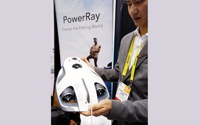 Alan Wang, technical support engineer with Powervision Robot Corp., shows off the PowerRay fish-finder equipped fishing drone. Reuters