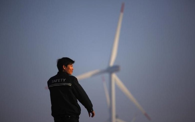 A security guard stands in front of windmills used to generate energy in Shanghai November 28, 2011. Reuters