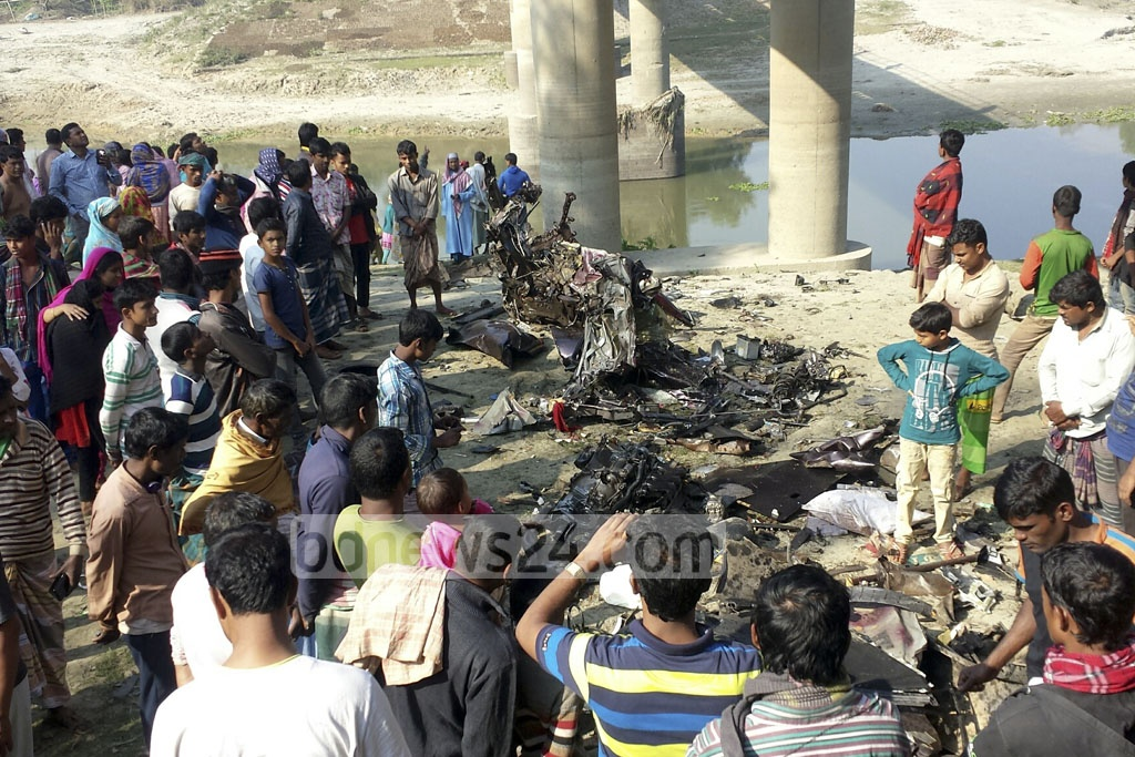 Crowd gather around what remains of a private car under a rail bridge after it was hit and dragged by the Kolkata-bound Maitree Express at Gazipur's Kaliakoir. Five people were killed in the accident on Sunday.