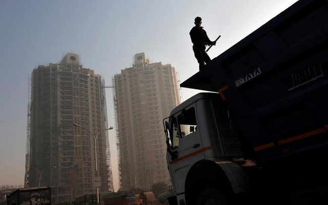 A labourer stands on a truck carrying construction materials at a construction site of residential buildings in Noida on the outskirts of New Delhi November 29, 2013. Reuters