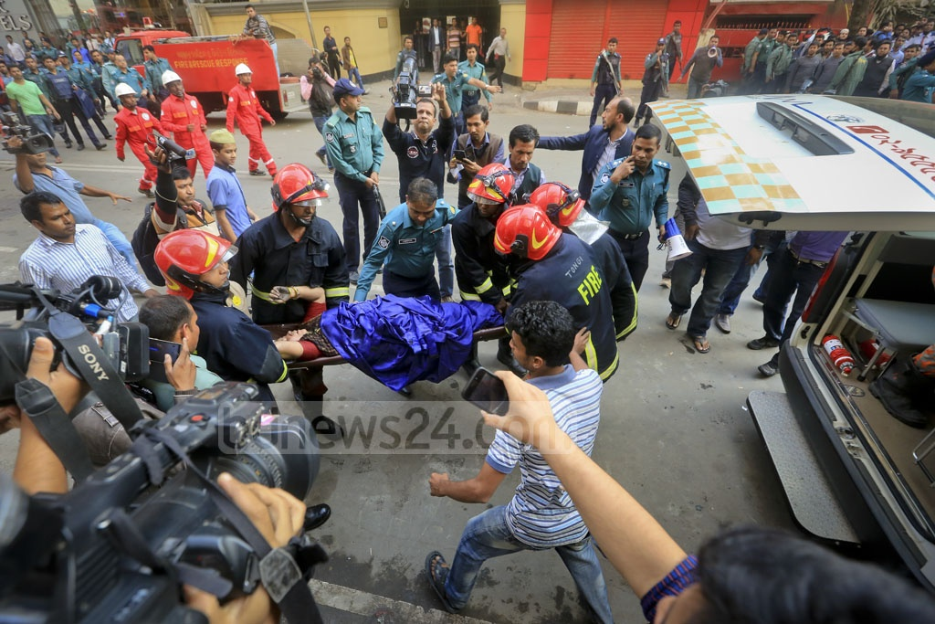Fire crews carry an wounded woman to ambulance after rescuing her from a high-rise, which caught fire in the capital's Banani on Monday.