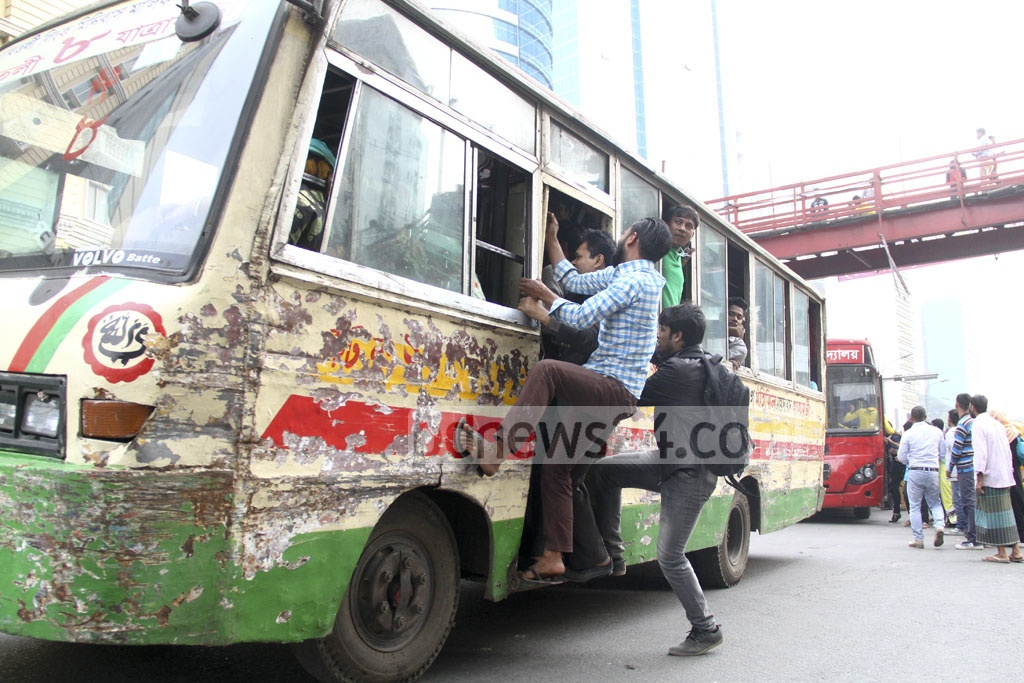 Desperate for a ride, commuters hang on to a bus door as Tuesday's Awami League rally triggered a shortage of public transport. Photo: abdul mannan