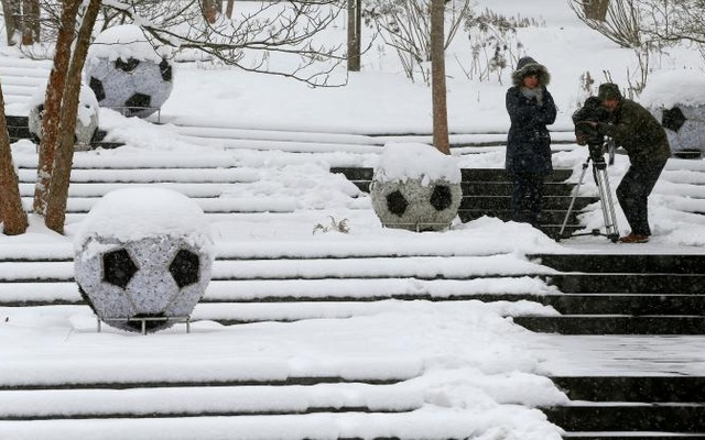 A cameraman takes pictures during a snowfall in front of the FIFA headquarters in Zurich, Switzerland, January 10, 2017. Reuters