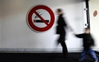 A woman walks past a ''No Smoking'' sign in Nice, south-eastern France, February 12, 2007. Reuters