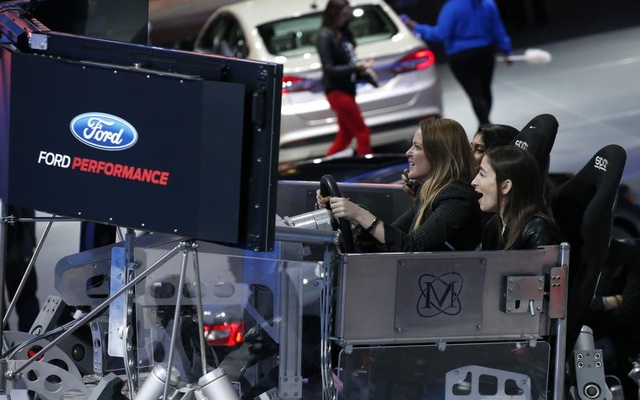 People try out a racing simulator in the Ford presentation area. Reuters