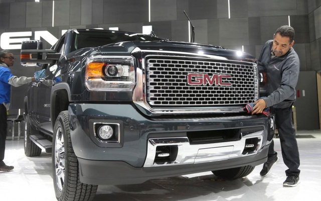 Detailers clean a 2017 GMC Sierra Pick-up truck on display before the start of press days. Reuters