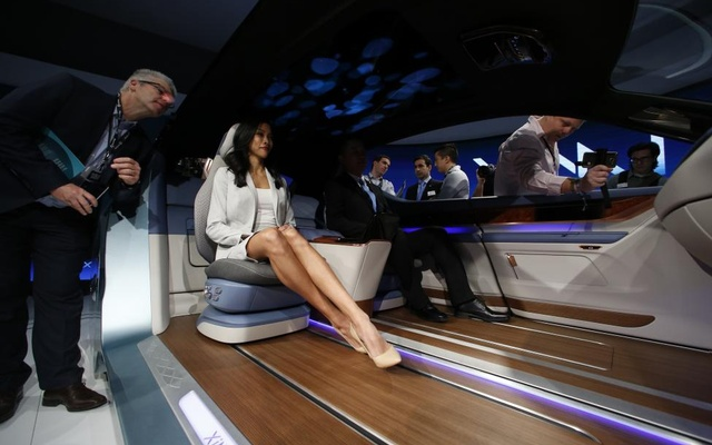 People try out the XIM 17 vehicle interior concept unveiled by Yanfeng Automotive Interiors. Reuters