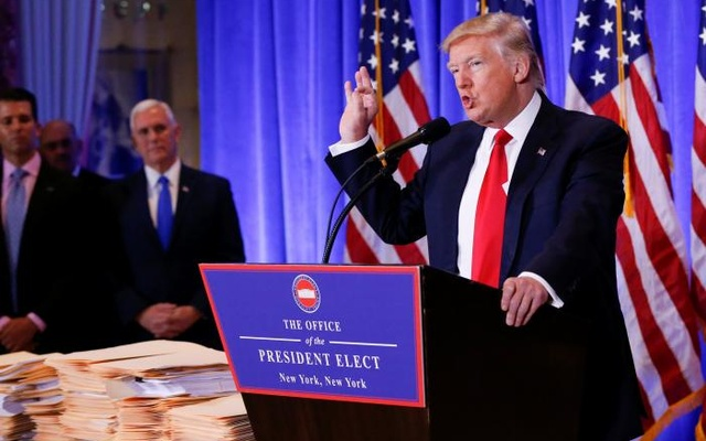 Vice President-elect Mike Pence is seen in the background as US President-elect Donald Trump speaks during a press conference in Trump Tower, Manhattan, New York, US, January 11, 2017. Reuters