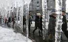 People walk past icicles, which hang from the roof of a building in a street in central Kiev, Ukraine. REUTERS