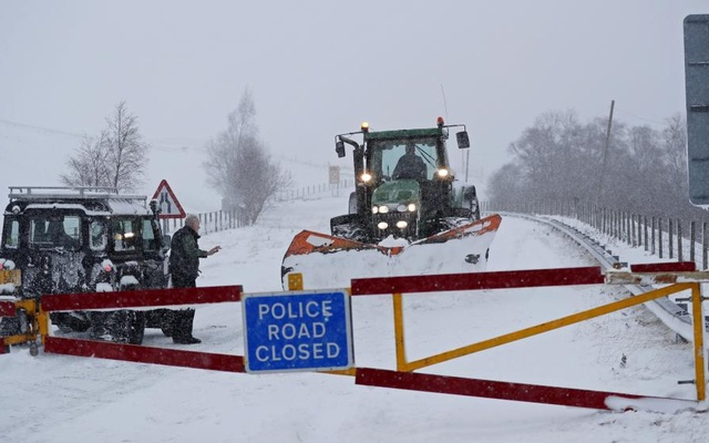 A tractor with a snow plough clears snow from the closed A93 at Spittal of Glenshee, in Scotland, Britain. REUTERS