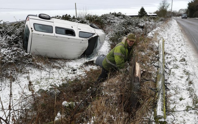 A farmer inspects a taxi after it crashed onto his land in icy conditions near Coalville in Britain. REUTERS