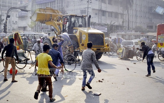 Protesters attack a Dhaka South City Corporation vehicle with stones during the eviction drive on Sunday. The Corporation started clearing the roads and pavements in Gulistan and adjacent areas which were occupied by the hawkers.