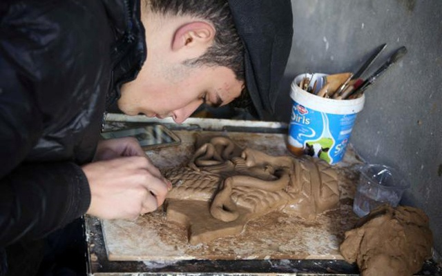 Ninos Thabet, an 18-year-old Christian who studied art at Mosul University, creates miniature replicas of statues destroyed by militants when they overran the 3,000-year-old Assyrian city of Nimrud 2-1/2 years ago, in Erbil, Iraq, January 13, 2017. Picture taken January 13, 2017. Reuters