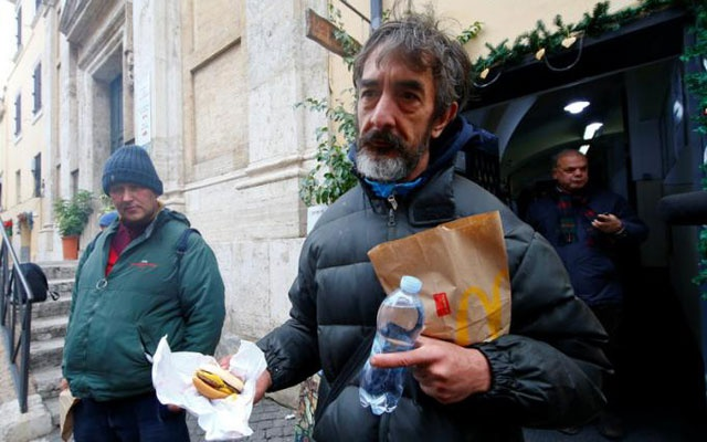 A needy man holds a cheeseburger donated by McDonald's to a charity organisation which bestowed them at a walk-in clinic in Rome, Italy January 16, 2017. Reuters