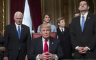US President Donald Trump in the Oval Office at the White House flanked by Vice President Mike Pence (left), House Speaker Paul Ryan (right), son Barron Trump and wife Melania Trump (behind) in Washington, US, Jan 20, 2017. Reuters