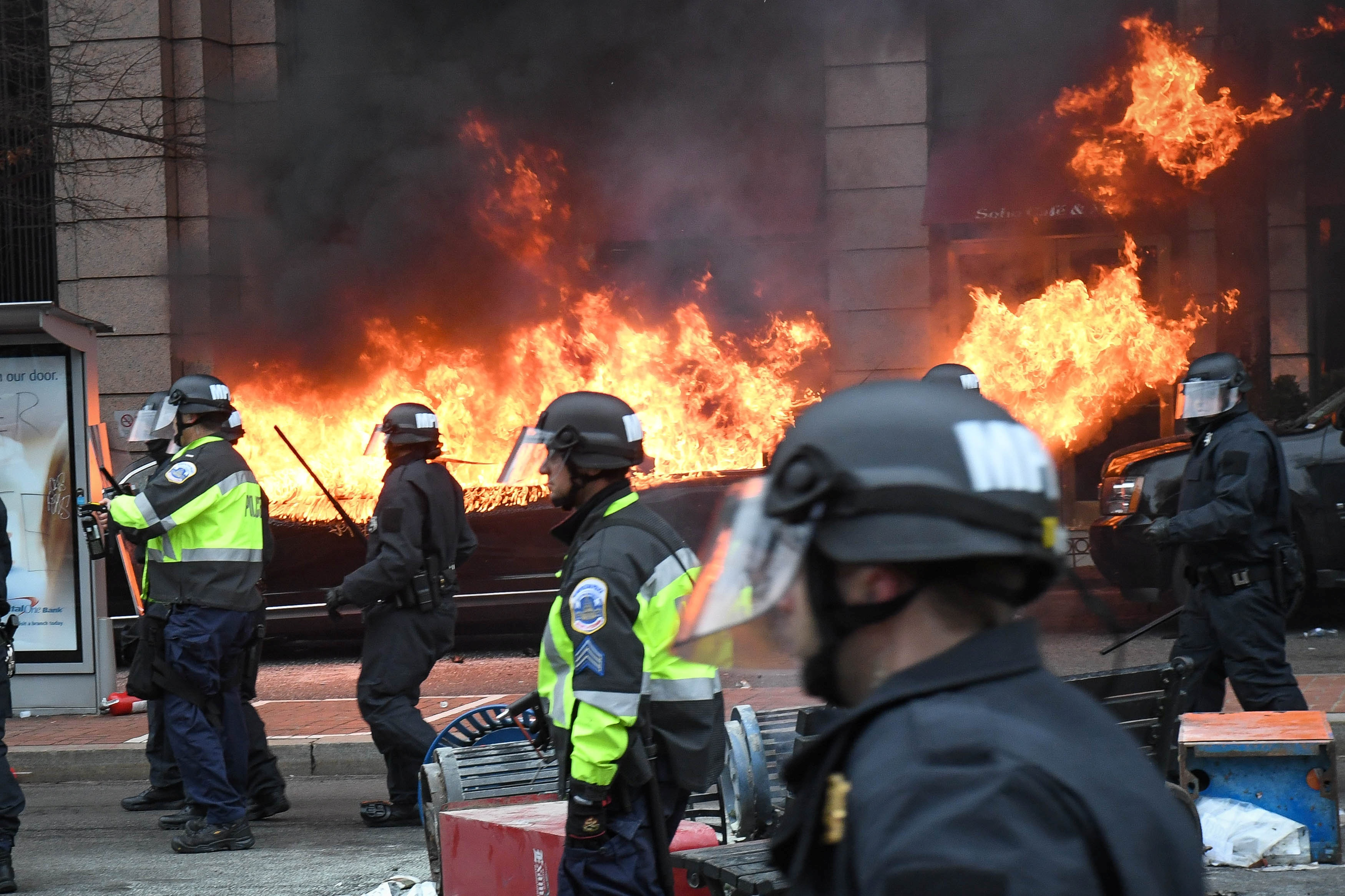 Police stand near a limousine which was set ablaze during a protest against US President Donald Trump on the sidelines of the inauguration in Washington, DC, US, on Jan 20, 2017. Reuters
