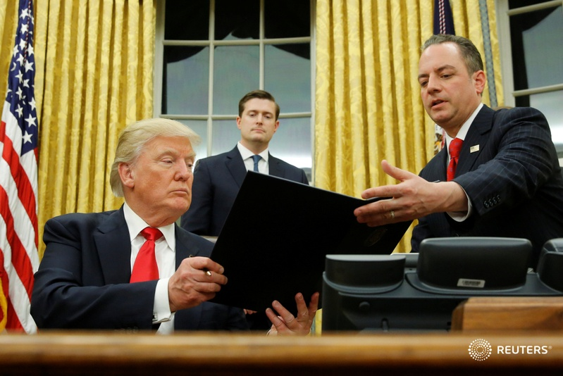 US President Donald Trump hands Chief of Staff Reince Priebus (right) an executive order that directs agencies to ease the burden of Obamacare, after signing it in the Oval Office in Washington, US, Jan 20, 2017. Also pictured is White House Staff Secretary Rob Porter (centre). Reuters