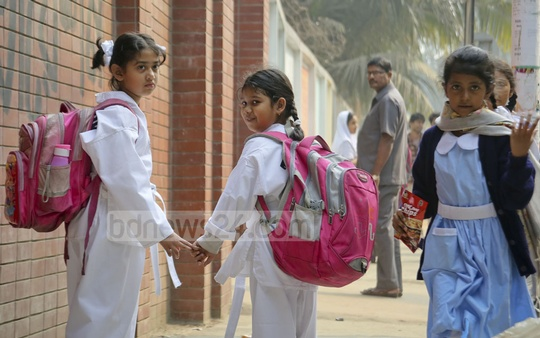 Despite court directives to reduce the weight of the schoolbag, many children are forced to carry heavy bags to schools packed with nearly a dozen textbooks and separate homework copies. The picture was clicked on Monday in front of Dhaka's Udayan Higher Secondary School. Photo: asaduzzaman pramanik