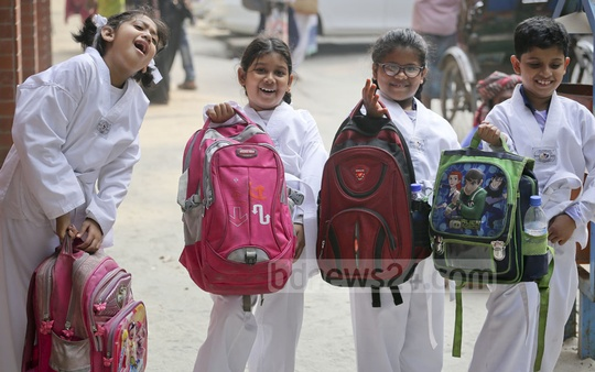 Whose bag weighs how much? These four tiny tots from Dhaka's Udayan Higher Secondary School try to find out the answer! Photo: asaduzzaman pramanik