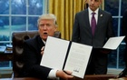 US President Donald Trump holds up the executive order on withdrawal from the Trans Pacific Partnership after signing it as White House Chief of Staff Reince Priebus stands at his side in the Oval Office of the White House in Washington January 23, 2017. Reuters