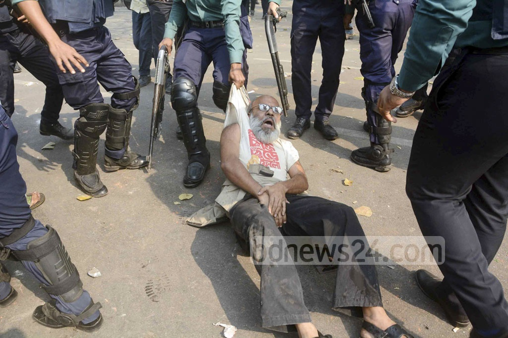 Police drag a protester away from the water cannon truck during demonstrations against the Rampal power plant project in Dhaka on Thursday. Photo: asif mahmud ove