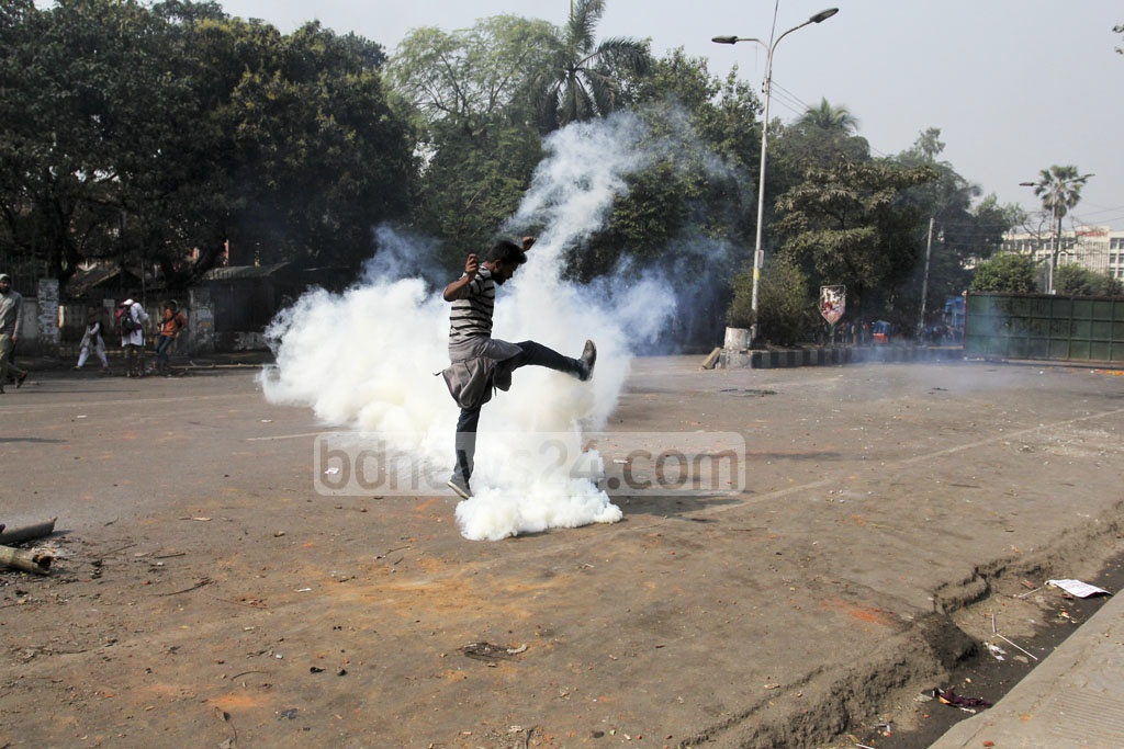A protester attempts to kick a tear gas canister back towards police during demonstrations against the Rampal power point project in Dhaka on Thursday. Photo: asif mahmud ove