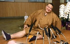 New Year Grand Sumo Tournament winner ozeki Kisenosato Yutaka stretches his legs during a press conference at his Tagonoura stable in Tokyo, a day after ending the tournament with a 14-1 record, in this photo taken by Kyodo on Jan. 23, 2017. Reuters/Kyodo