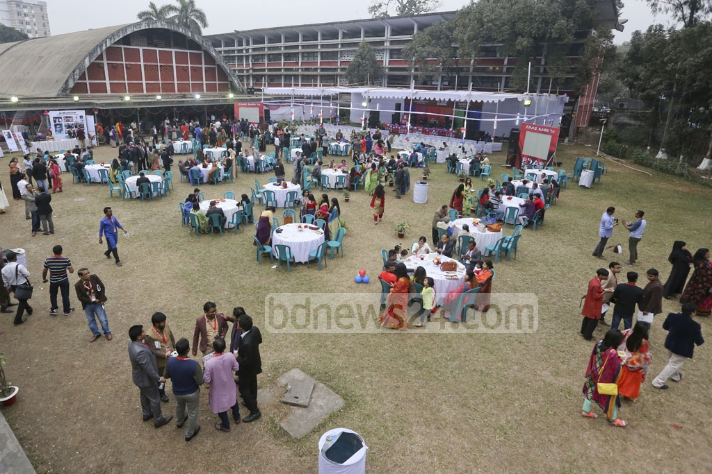 The alumni having chitchats in small crowds on the green lawn of the TSC.