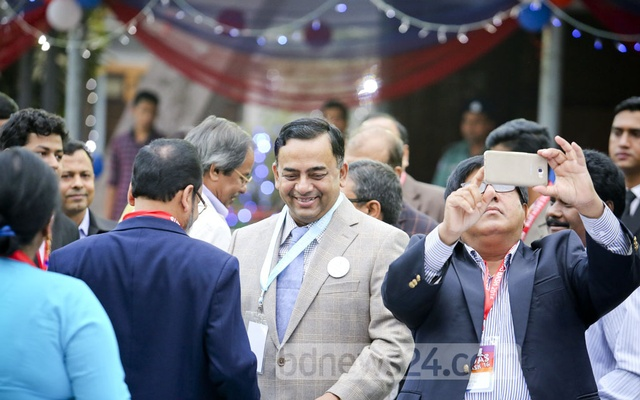 RAB Director General Benazir Ahmed smiles while chatting with friends.