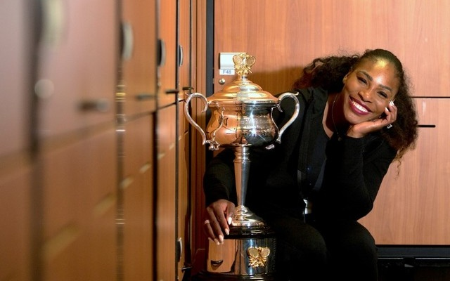 Serena Williams of the U.S. sits next to the trophy after winning the Women's singles final against sister Venus at the Australian Open tennis tournament in Melbourne, Australia