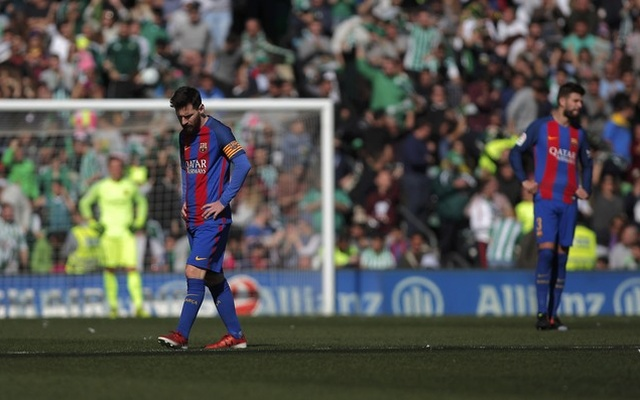 Barcelona's Lionel Messi and Gerard Pique react after Real Betis scored a goal during the match
