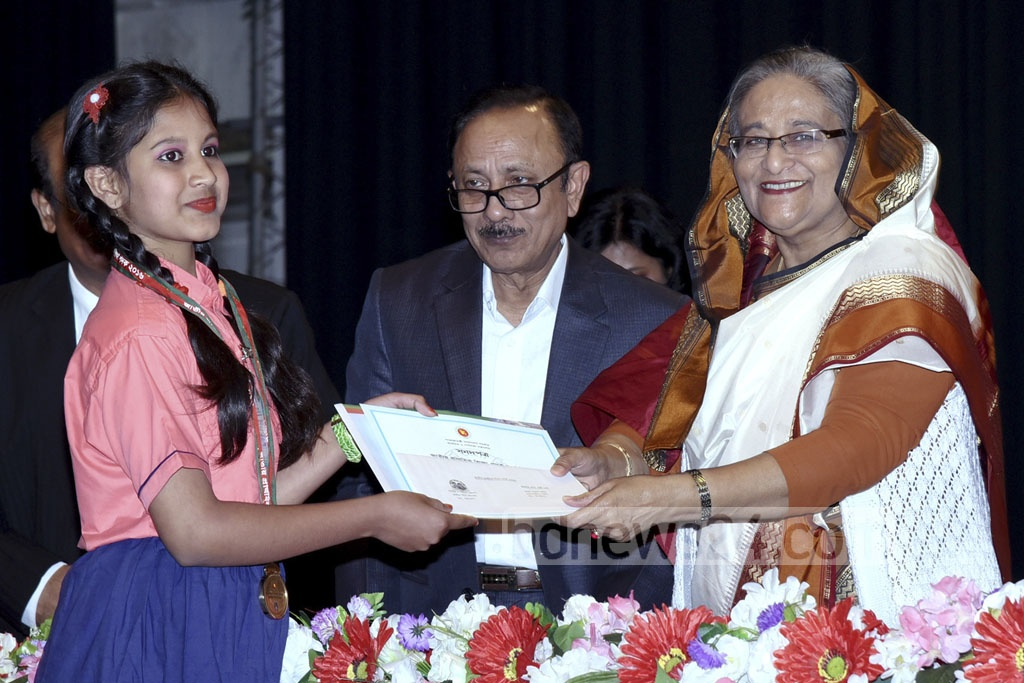 Prime Minister Sheikh Hasina presents National Primary School Level Sports and Culture Awards at the inaugural ceremony for Primary Education Week at the Osmani Memorial Auditorium in Dhaka on Sunday. Photo: Saiful Islam Kallol