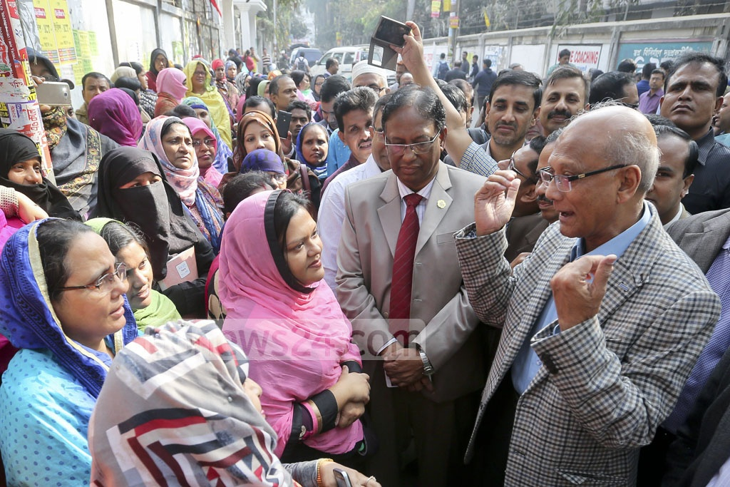 Education Minister Nurul Islam Nahid talks to guardians of SSC candidates waiting outside the exam centre at Dhaka's Government Laboratory High School on Thursday. Photo: asaduzzaman pramanik