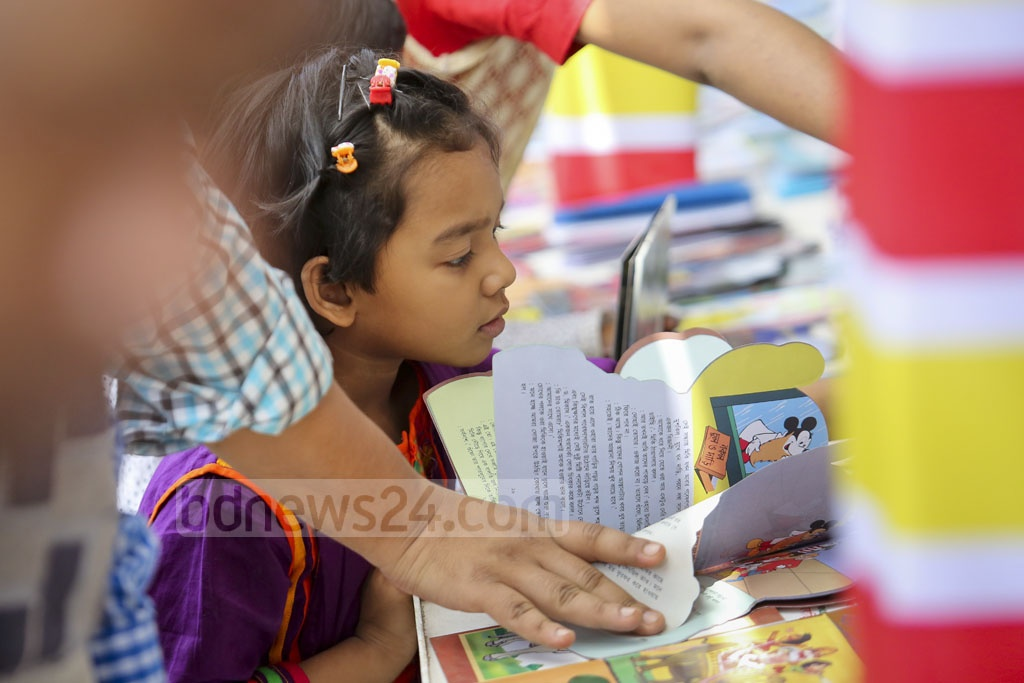 A child checks what is in the book for her during the first Children's Hours of Amar Ekushey Book Fair at Suhrawardy Udyan on Friday. Photo: asaduzzaman pramanik