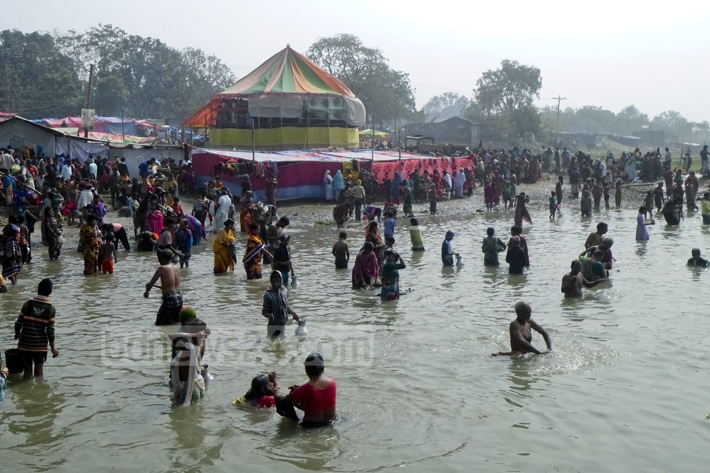 Hindu devotees take part in 'Gangasnan' (Holy Bath) in the Torttipur Pagla River in Chanpainawabganj's Shibganj on Friday.