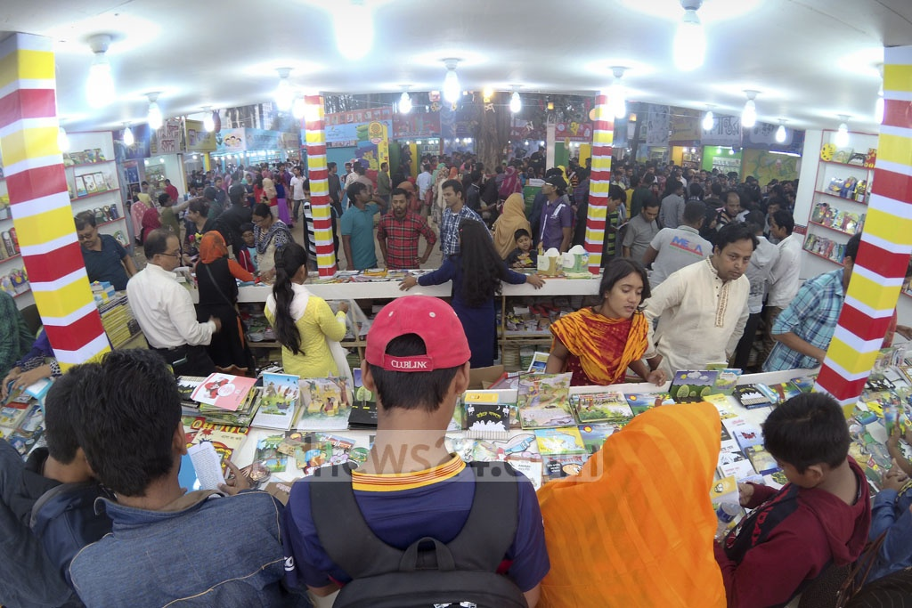 Customers browse books at a stall of Amar Ekushey Book Fair at Suhrawardy Udyan on Friday. Photo: abdul mannan