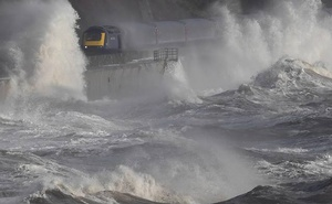 Waves hit a train during heavy seas and high winds in Dawlish. Reuters