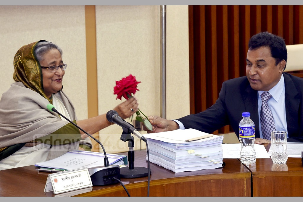 Planning Minister AHM Mustafa Kamal greets Prime Minister Sheikh Hasina at the ECNEC meeting on Tuesday on the occasion of Rose Day on the eve of the start of Valentine's Week. Photo: Saiful Islam Kallol