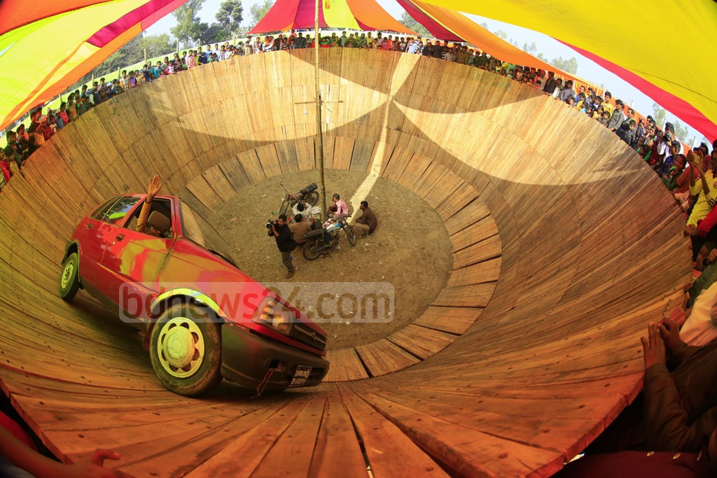 A stuntman driving a car inside a specially-made well at the Poradah Fair in Bogra.