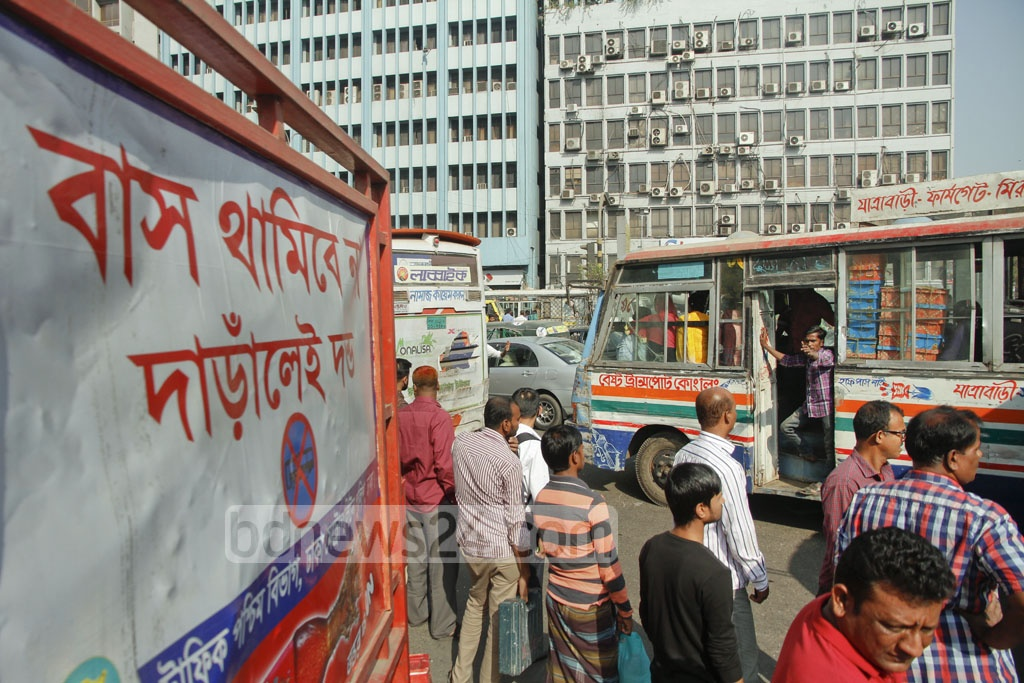 Despite signboards asking buses not to stop, they do so at Dhaka's Kawran Bazar. Photo: tanvir ahammed