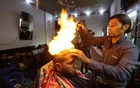 Palestinian barber Ramadan Odwan styles and straightens the hair of a customer with fire at his salon in Rafah, in the southern Gaza Strip February 2, 2017. Reuters