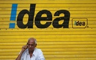 A man speaks on his mobile phone as he sits in front of a shop displaying the Idea Cellular Ltd's logo on its shutter in Mumbai, India, April 28, 2014. Reuters