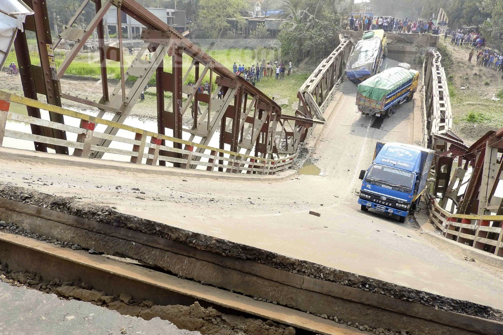 The bridge on Chitra River caves in to the weight of three trucks on the Jessore-Magura Highway on Monday.