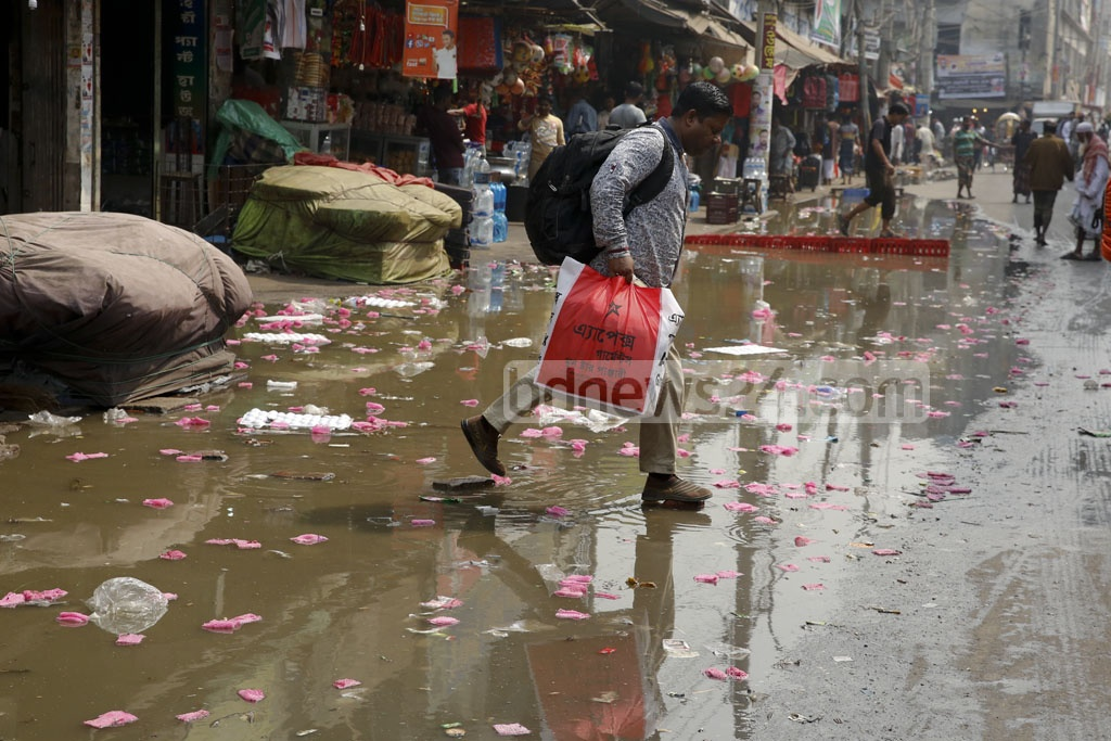 Dhaka City Corporation cleaning staff says polythene and plastic packets have clogged the drains, causing sewerage to overflow on the Sadarghat Road in Old Dhaka. Photo: mostafigur rahman