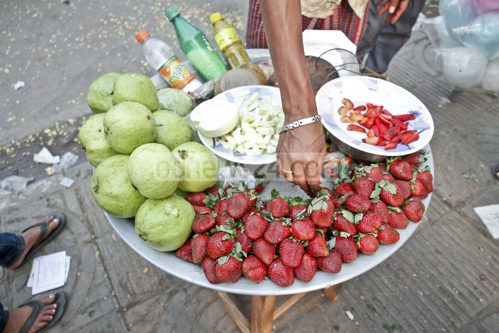 Vendors sell 100g of spiced strawberry for Tk40 at Dhaka's Central Shaheed Minar alongside more traditional treats like spiced guava and hog plum. Photo: tanvir ahammed