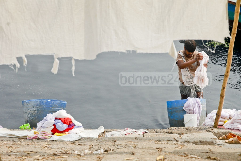 Bed-sheets and pillow covers of Orion Renal and General Hospital being washed in the polluted Burhiganga water.