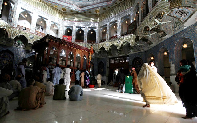 FILE PHOTO: A woman clad in burqa walks in the hallway of the tomb of Sufi saint Syed Usman Marwandi, also known as Lal Shahbaz Qalandar, in Sehwan Sharif, in Pakistan's southern Sindh province, Sept 5, 2013. Reuters