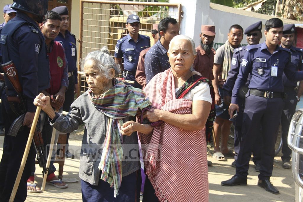 An elderly voter is helped away from the polls in Rangamati's Baghaicharhi on Thursday.