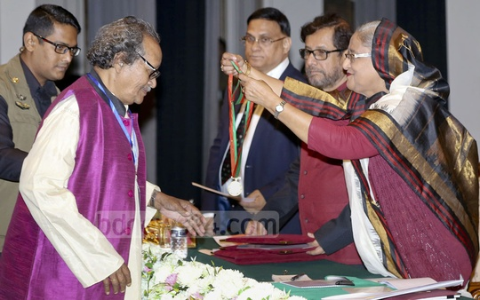 Prime Minister Sheikh Hasina presents an Ekushey Padak winner with a medal during a ceremony at Dhaka's Osmani Memorial on Monday.