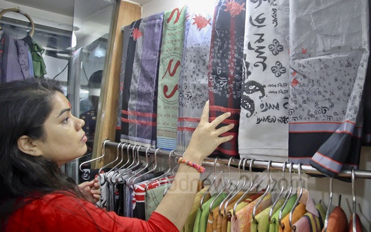 A customer looks at sarees that celebrate Bangladesh's love for its language, ahead of International Mother Language Day.